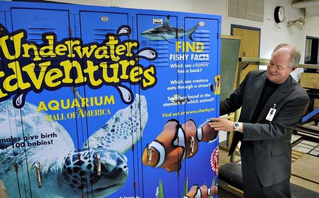 Superintendent Jim Johnson of Monticello Schools shows a display of possible locker advertising under consideration at several school districts